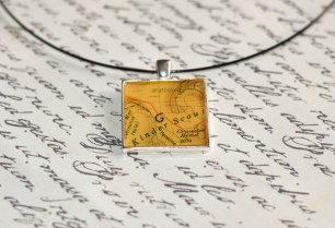 A photograph of the Kinder Scout pendant placed on top of a handwritten letter