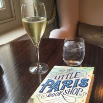 A photograph of a glass of Prosecco on a table alongside Emma's book
