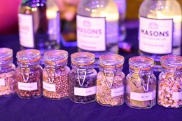 A row of small bottles full of botanicals that go into Masons Gin