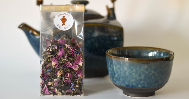 A photograph of the finished tea in a bag with a blue tea cup and tea pot as props in the background