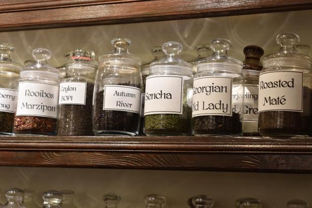 A photograph of tea jars lined up on a shelf