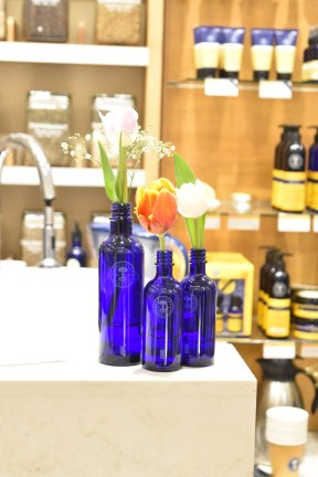 A photograph of three iconic blue bottles filled with tulips