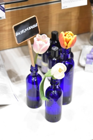 A photograph of more blue bottles with tulips and a small chalkboard with #NYRCambridge