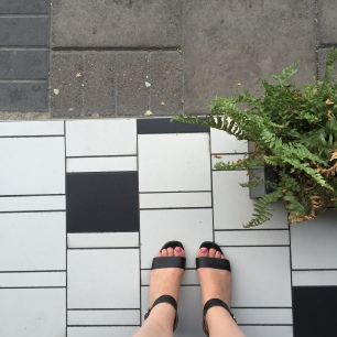 A top-down photograph of Emma's feet on the floor tiles outside NOVI that are at a different angle to the pavement slabs