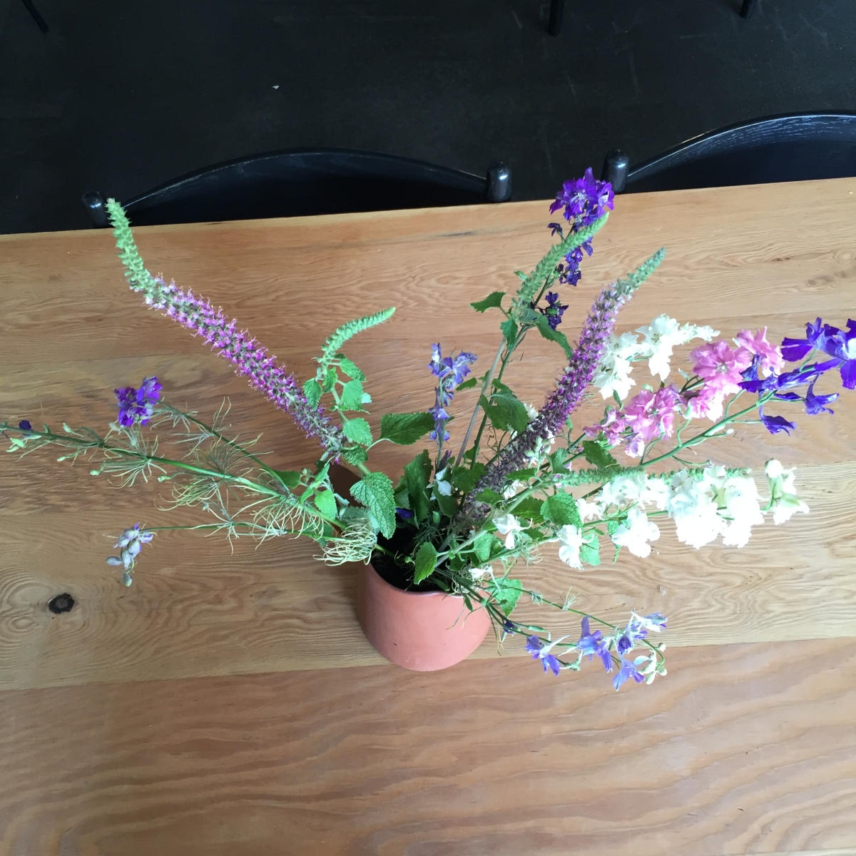 A photograph of a summer bouquet on a table at NOVI. There are white, pink, and blue flowers.