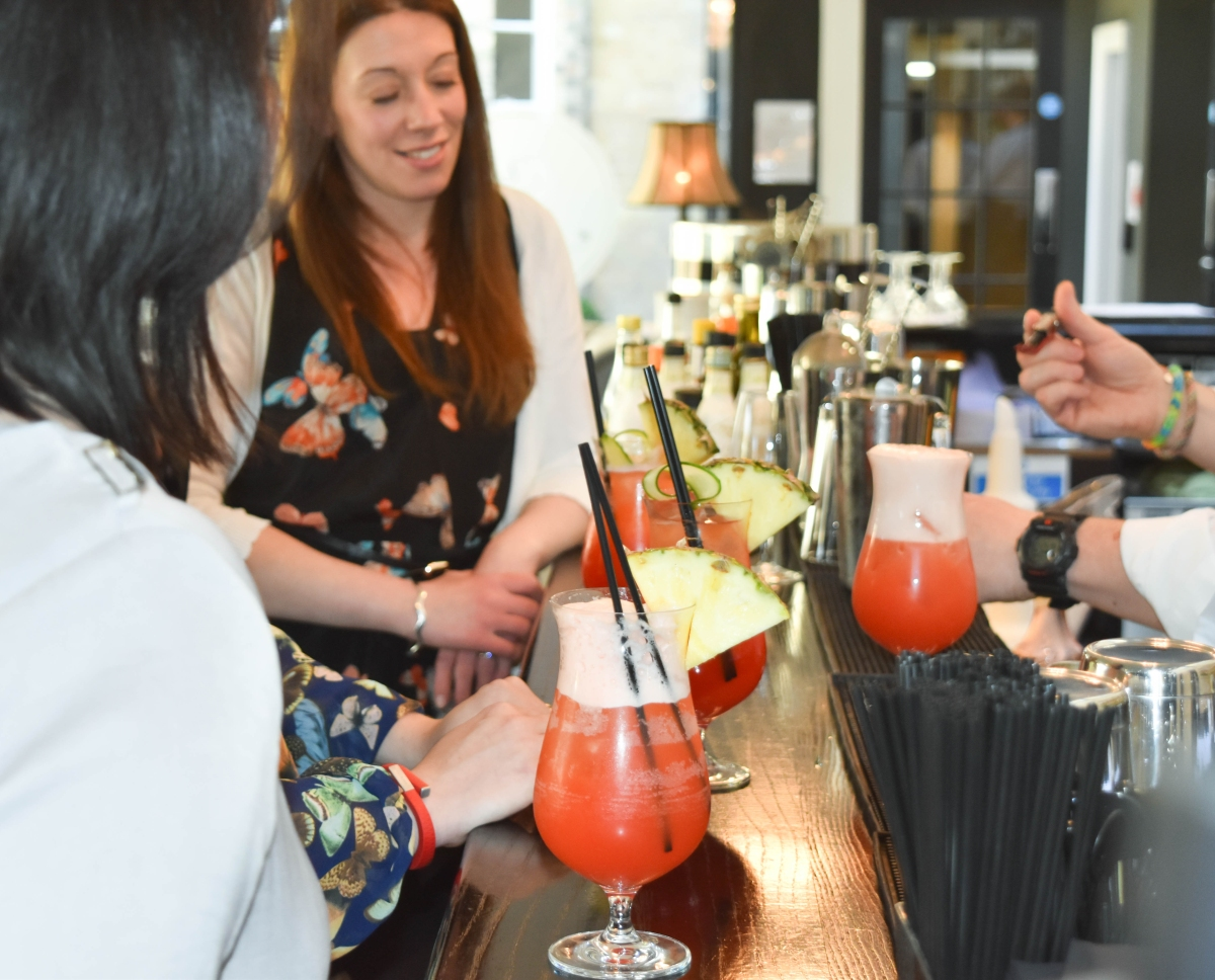 A photograph of a group at the bar being shown how to make a non-alcoholic Bora Bora Brew