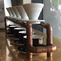 A photograph of a row of ceramic coffee filters suspended over coffee cups
