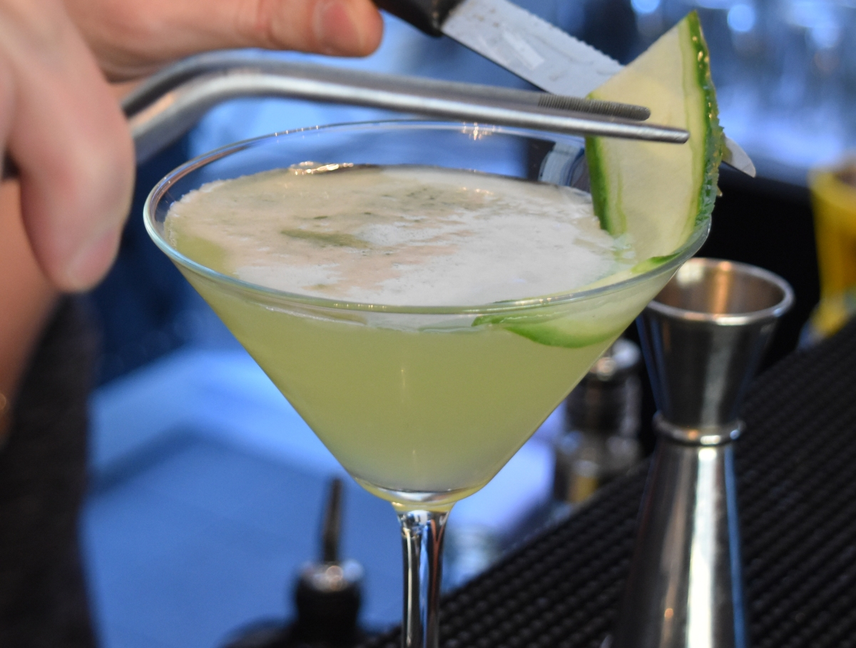 A photograph of a thin slice of cucumber being placed carefully into a glass of Cucumber Martini