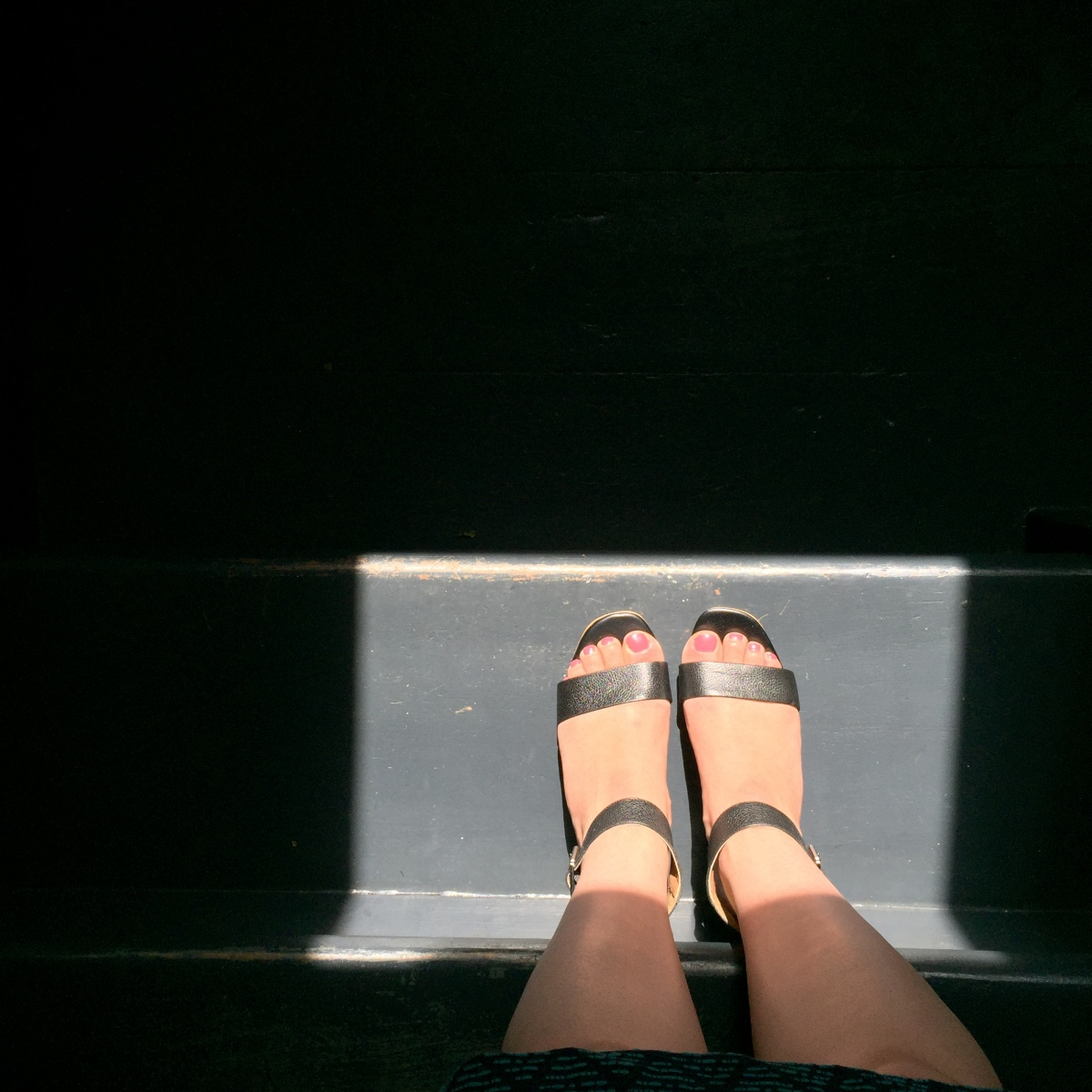 A top-down photograph of Emma's feet in black leather sandals standing on a step with sunlight shining on Emma's feet in the bottom right corner