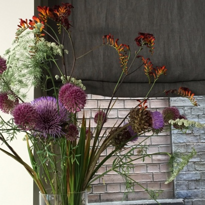 A photograph of flowers by a window in NOVI