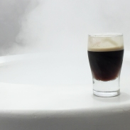 A photograph of a Guinness shot glass on the right side of the photo with white tones in the rest of the photograph to demonstrate negative space and rule of thirds
