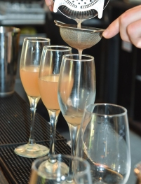 A photograph of a cocktail being poured carefully through a sieve into three Champagne flutes