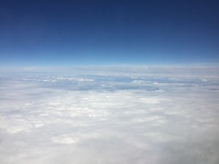 A photograph of the view from an aeroplane with the top third blue sky and bottom two thirds fluffy white clouds to demonstrate texture
