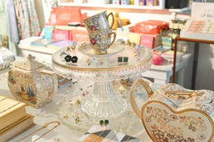 A photograph of a centre piece on a table. A glass cake stand is topped with pretty tea cups and surrounded by jewellery