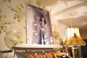 A photograph of a large Emily and Rose marketing print sitting on top of a clothing rail with pretty floral wallpaper decorating the wall behind and two large lampshades either side