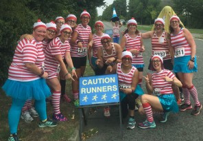 "A photograph of the team grouped behind a road sign saying ""Caution Runners"""