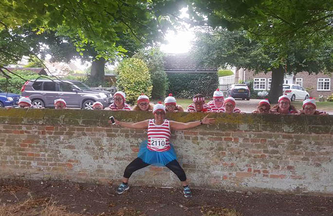 A photograph of the girls recreating the vintage Chad cartoon be lining up behind a wall with just the heads and hands visible