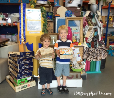 A photograph of the two boys proudly holding up their finished memory boxes.