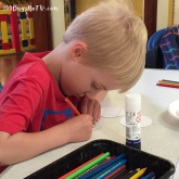 A photograph of Ollie concentrating hard on his colouring.