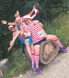 A photograph of five wallys on a fallen tree recreating the Oops Upside Your Head dance