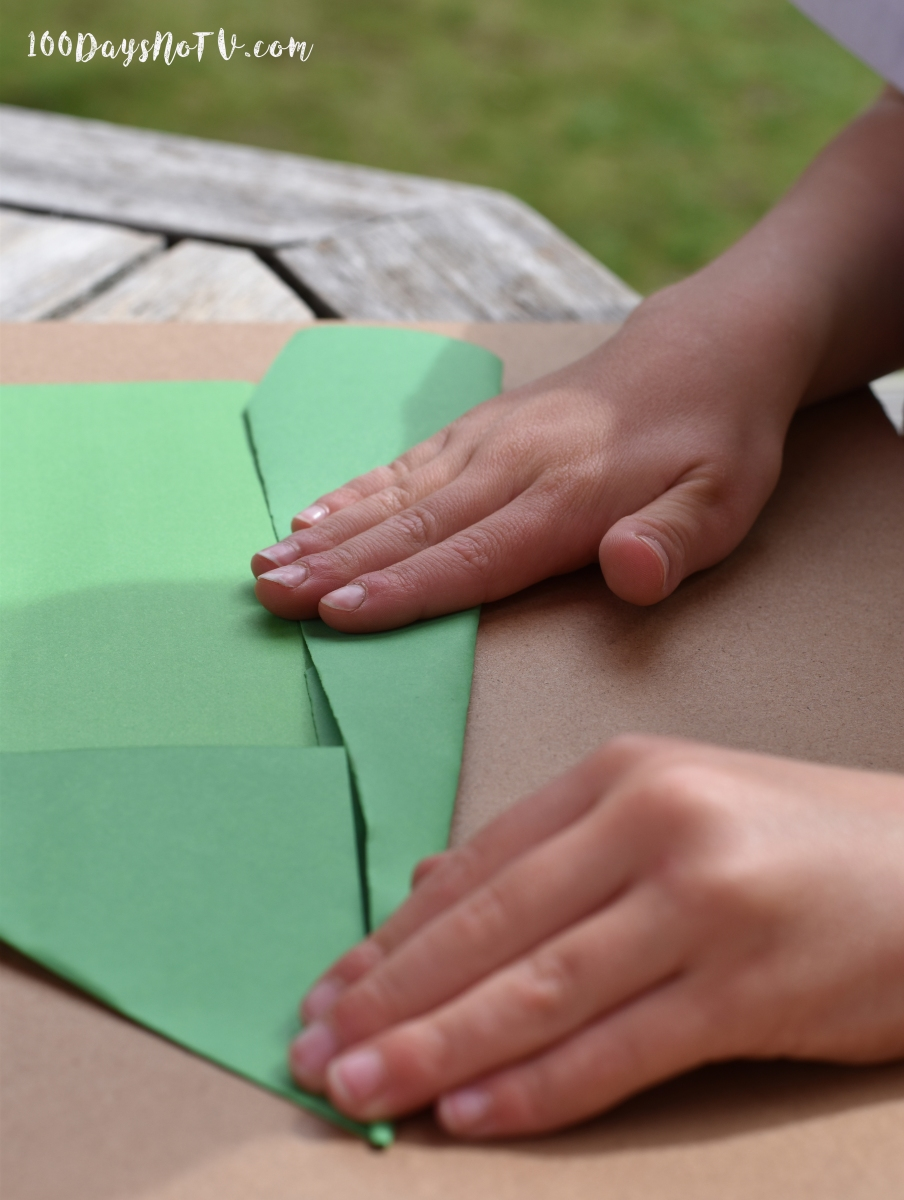 A close up photograph of Ollie folding paper to make his green plane.