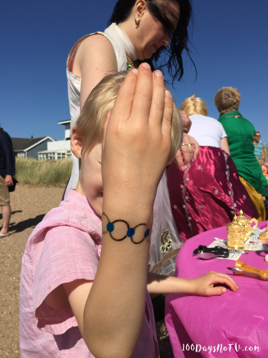 A photograph of Ollie holding his arm up to show his bracelet tattoo.