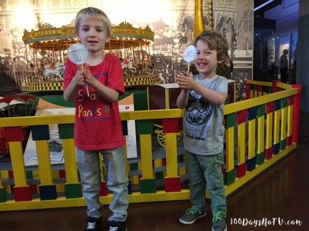 A photograph of Ollie and Ben using their thaumatropes. They rotate them between their hands quickly and you can see the images merge.