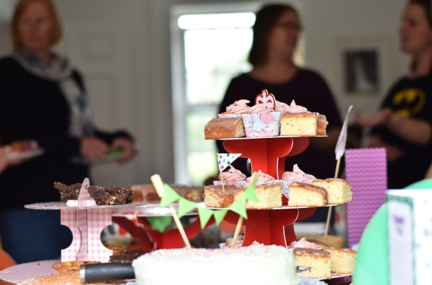 A photograph of the cake-covered table with Emma's friends in the background in full conversation
