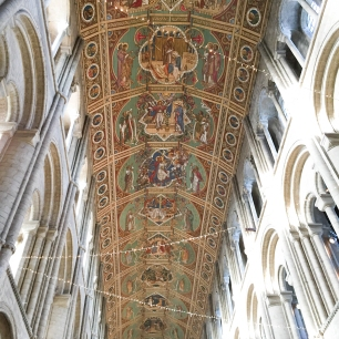 A photograph of the nave ceiling at the 900 year old Ely Cathedral with criss-cross fairy lights
