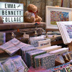A photograph of Emma Bennett Collage's stall with her products and a lightbox with her name