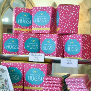 "A photograph of pink stacked boxes containing marshmallow ""hugs"""
