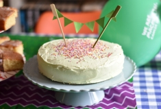 A photograph of a sponge cake covered in green icing with handmade green paper bunting hanging on two sticks poked into the top of the cake