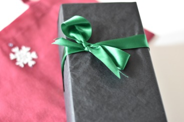 A photograph of the vodka that Emma bought, all boxed up and wrapped in black tissue paper and finished with a green ribbon bow