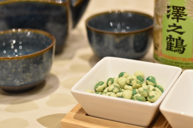 A photograph of a white square dish of wasabi peas, a snack for Rob and Emma to keep them going! Also in shot are two blue bowl-shaped cups and a bottle of sake.