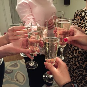 "A photograph of Emma and five friends bringing their glasses of prosecco together for a ""Cheers!"""
