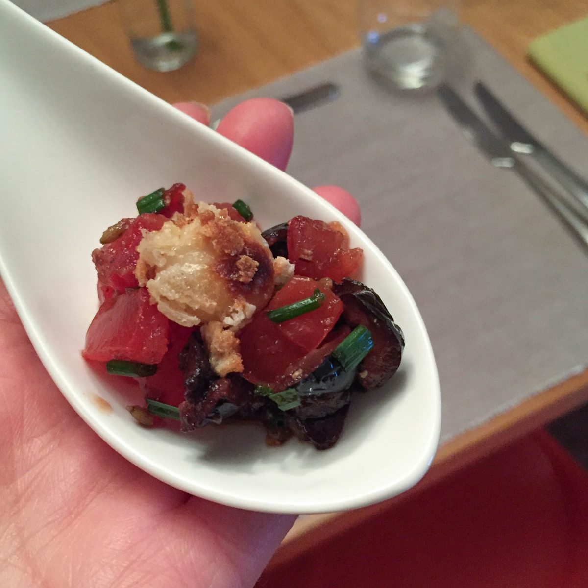 A photograph of the first canape: deep fried macadamia nuts in a tomato and olive salsa, served on a white ceramic spoon