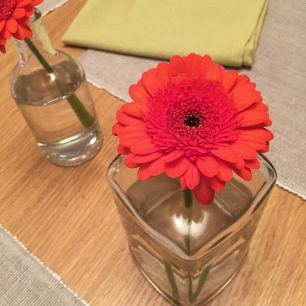 A photograph of two single orange gerbera flowers in clear vases. Part of Emma's table decor.