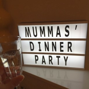 "A photograph of a lightbox saying ""Mummas Dinner Party"" with Emma's glass of Prosecco in the left-hand corner"