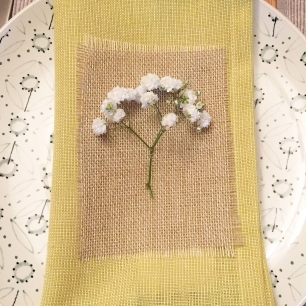 A photograph of a folded mustard-yellow napkin on top of a plate, and lying on top is a rectangle of hessian on top of which is a sprig of 'babies breath' flower, attached with a tiny silver thread