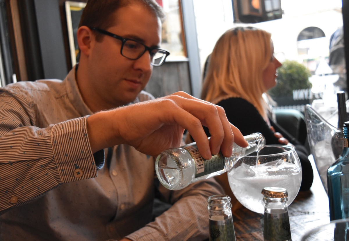 A photograph of Rob pouring tonic into his glass of gin.