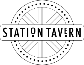 The Station Tavern signage. A black cartwheel shape with Station Tavern written in capitals on a banner across the middle.