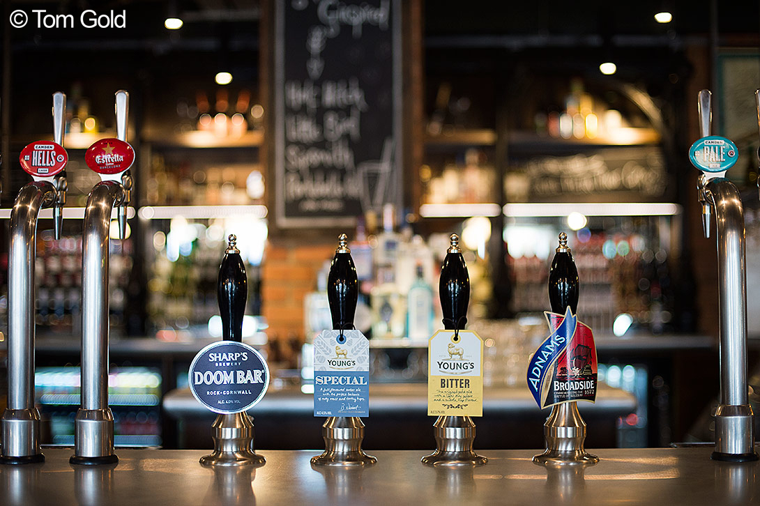 A photograph of seven beer taps, just a small selection of what they offer. Photo by Tom Gold.