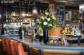 A photograph of the left side of the bar with silver bucket of prosecco bottles and a large vase of flowers. Photo by Tom Gold.