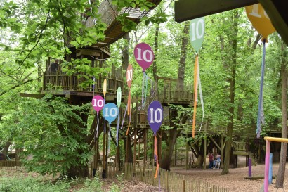 A photograph of wooden balloon shapes with 10 written on them. They're hanging below some suspended bridges.