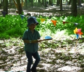 A photograph of Ben carrying his water balloon carefully on a large wooden spoon.
