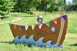 A photograph of Ben standing behind a large boat-shaped sign with his new Mildred puppet.