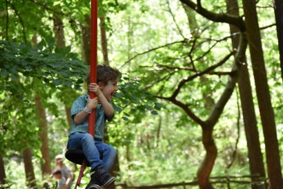 A photograph of Ben on the zip wire with a big smile on his face.