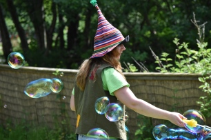 A photograph of a Twiggle (grown-up) making bubble with a bubble wand at the press event.