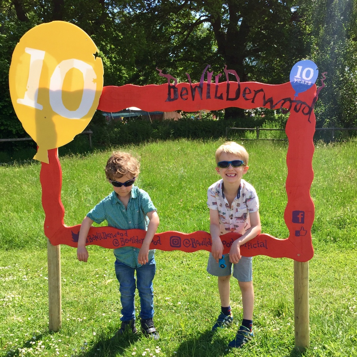 A photograph of Ben and Ollie posing in a wooden Instagram photo frame.