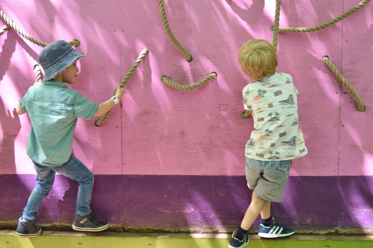 A photograph of Ben and Ollie walking across a wall with rope handles.